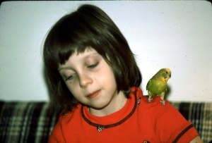 Yvonne at age eight with her pet parakeet